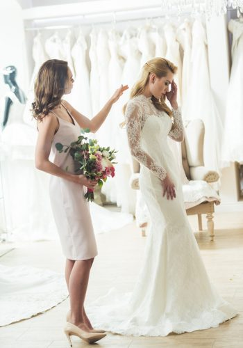 Upset bride with friend holding flowers in wedding salon